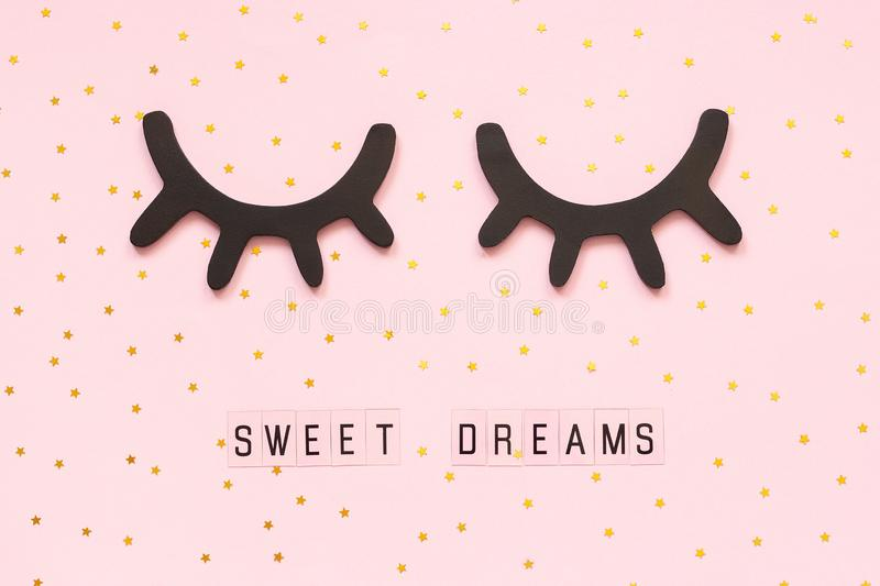 Text Sweet dreams and decorative wooden black eyelashes, closed eyes gold star on pink paper background. Concept Good. Text Sweet dreams and decorative wooden stock photos
