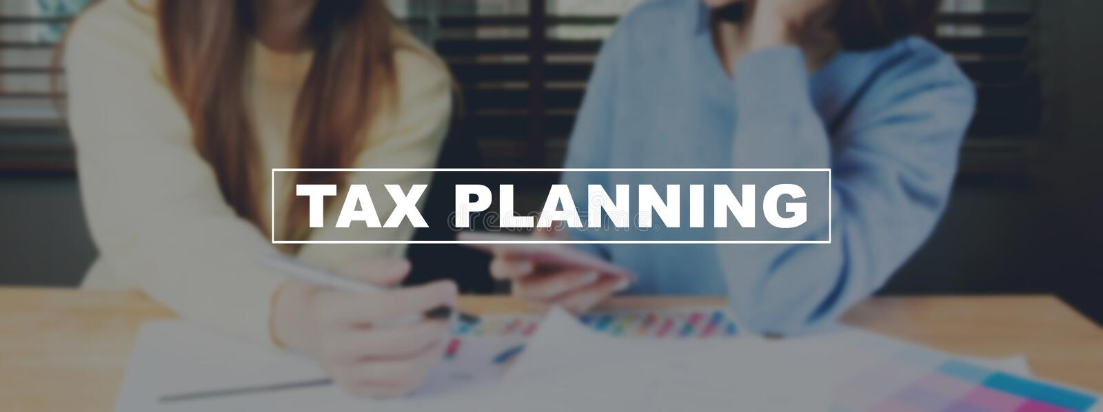 Text Tax planning on background women are working on smartphone. The concept of working with a lot of information. royalty free stock image