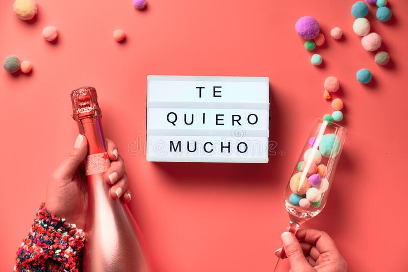 Text. `Te quero mucho` means I love you so much in English. Lightboard with  in Latino female hands, flat lay on pink background. Bottle of champagne, flute stock images