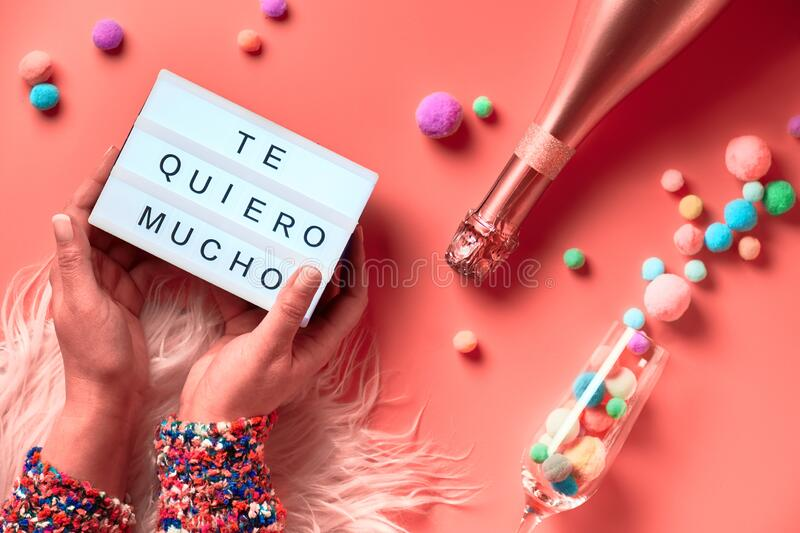 Text. `Te quero mucho` means I love you so much in English. Lightboard with  in Latino female hands, top view on pink background. Bottle of champagne, flute royalty free stock photo