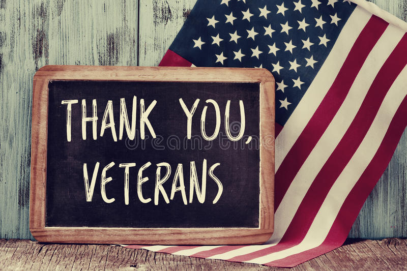 Text thank you veterans in a chalkboard and the flag of the US. The text thank you veterans written in a chalkboard and a flag of the United States, on a rustic royalty free stock image