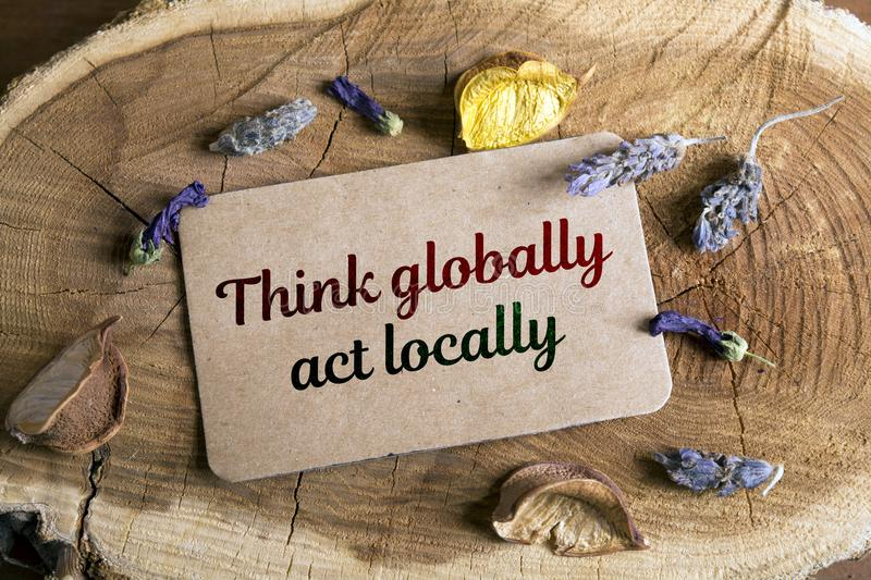 Think globally, act locally. Text Think globally, act locally in card on wood stock image