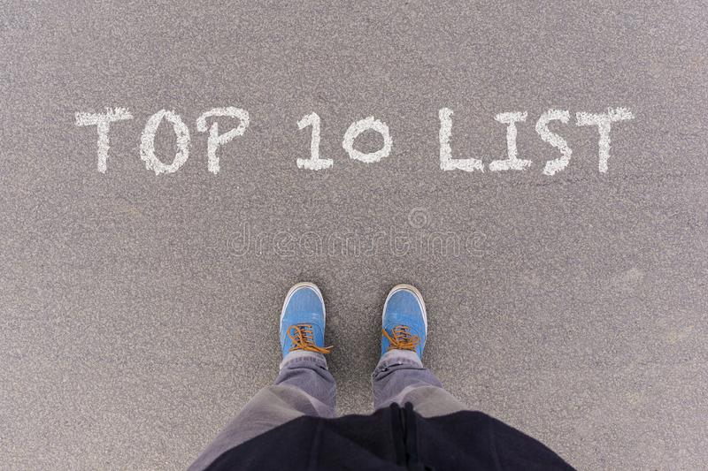 Text Top 10 written as text on asphalt ground, feet and shoes on royalty free stock photo