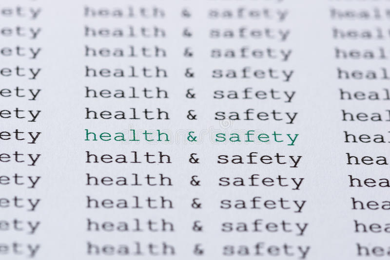 Text/typed phrase Health & Safety. The phrase health & safety highlighted in green amongst similar black text royalty free stock photo