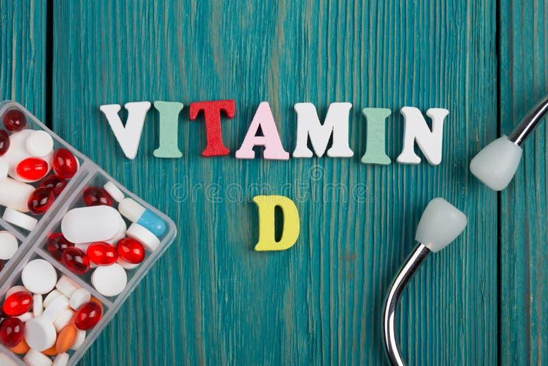 Text u. x22; Vitamin D& x22; von farbigen hölzernen Buchstaben, von Stethoskop und von Pillen lizenzfreie stockfotografie