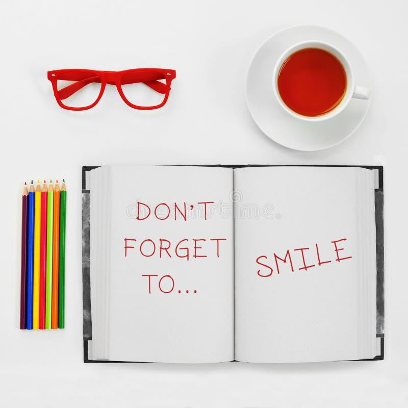 Text vergessen nicht zum Lächeln, das in einen Notizblock geschrieben wird stockbilder