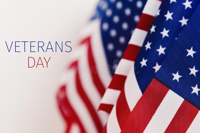 Text veterans day and american flags. Some american flags and the text veterans day against an off-white background royalty free stock photography