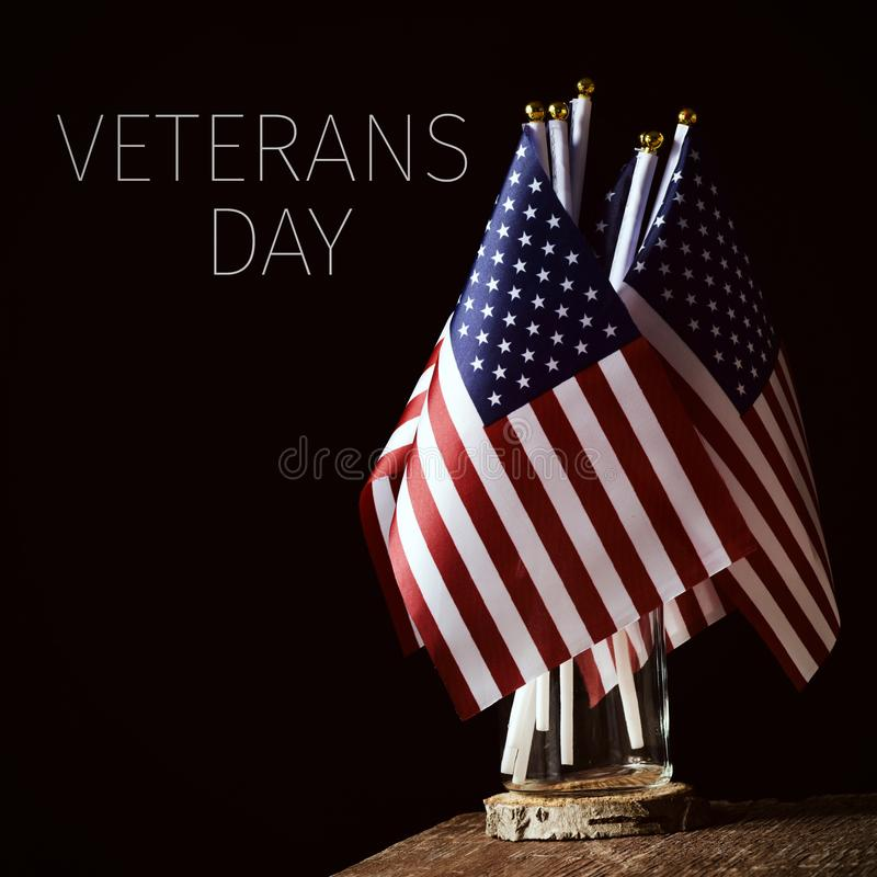 Text veterans day and american flags. Some american flags in a glass jar, on a rustic wooden surface and the text veterans day against a black background royalty free stock photos