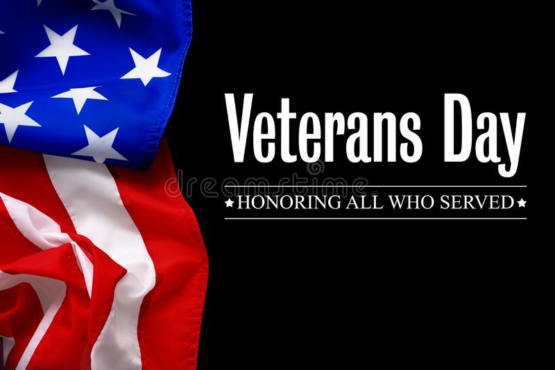 Text VETERANS DAY and USA flag on black background. Honoring all who served royalty free stock photo
