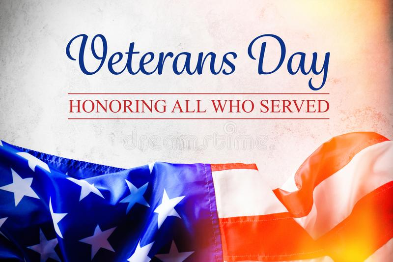 Text VETERANS DAY and USA flag on light background, top view. Honoring all who served stock images