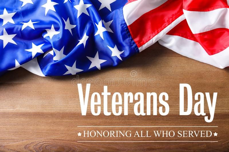 Text VETERANS DAY and USA flag on wooden background, top view. Honoring all who served royalty free stock images