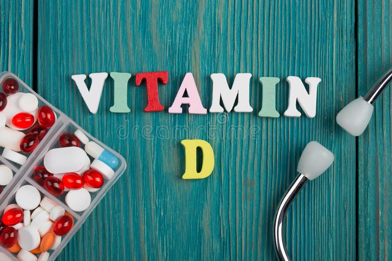 Text & x22;Vitamin D& x22; of colored wooden letters, stethoscope and pills royalty free stock photography