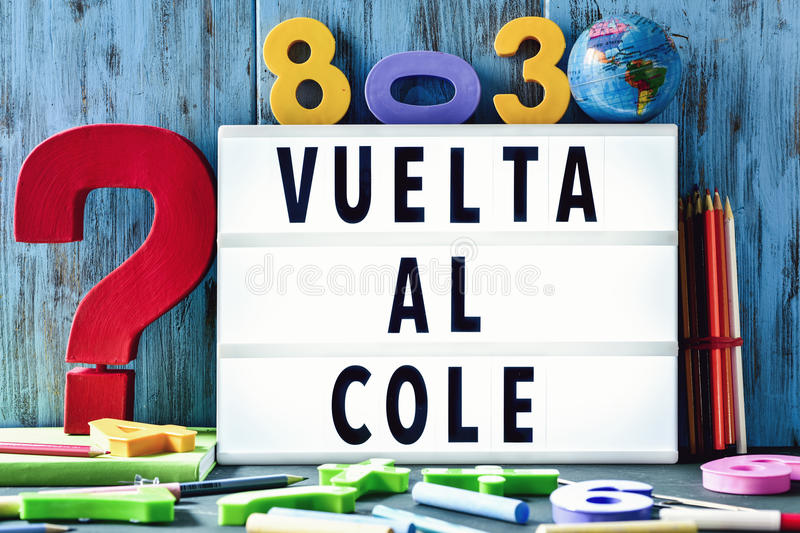 Text vuelta al cole, back to school in spanish. The text vuelta al cole, back to school in spanish, in a lightbox placed against a rustic wooden background royalty free stock image