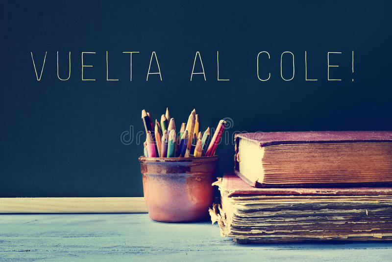 The text vuelta al cole, back to school in spanish, written in a. Some pencils in a pot, some old books on a blue school desk, and the text vuelta al cole, back stock image