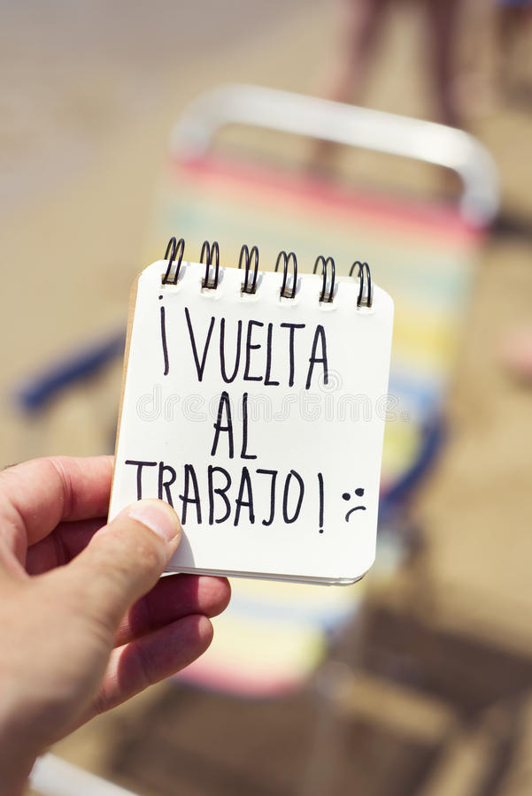 Text vuelta al trabajo, back to work in spanish. Closeup of a young man in the beach showing a spiral notepad with the text vuelta al trabajo, back to work in stock photography