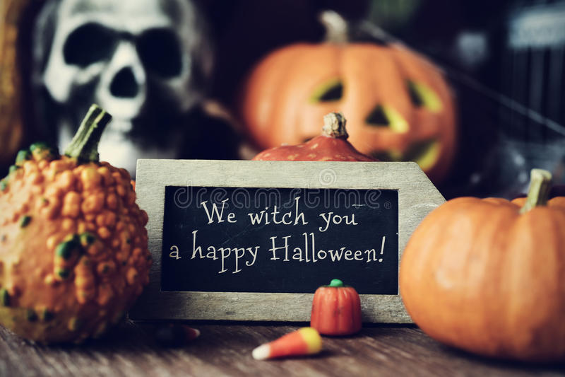 Text We witch you a happy Halloween in a chalkboard. A chalkboard with the text We witch you a happy Halloween, surrounded by some different pumpkins, placed on royalty free stock photo