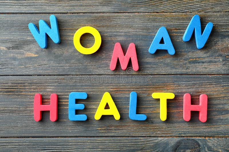 Text WOMAN HEALTH made of color letters on wooden background royalty free stock image