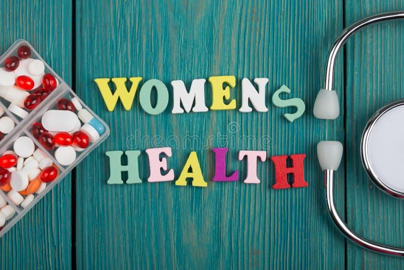 Text & x22; Women& x27; s-health& x22; av kulöra träbokstäver, stetoskopet och preventivpillerar royaltyfri foto