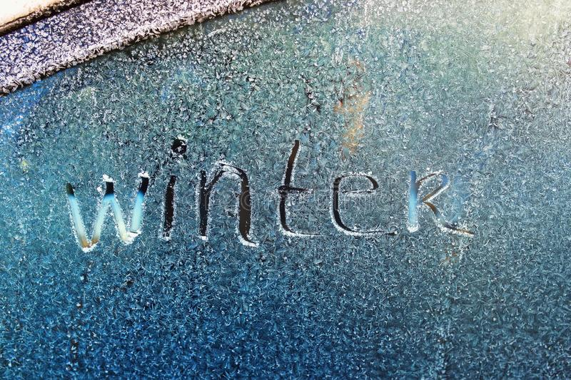Text word winter scraped on frosty glass covered with white frost crystals on car blue window on winter cold clear morning. Text word winter scraped on frosty stock photography