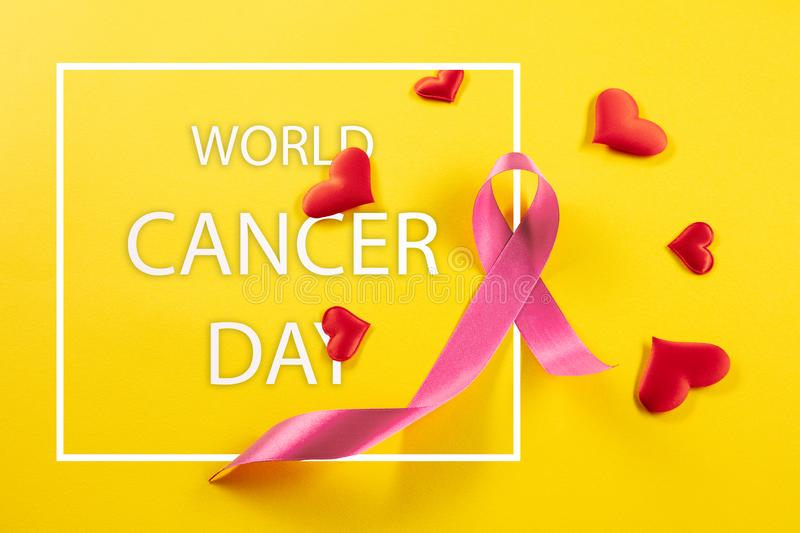 e13a4393117 The text world cancer day and a pink ribbon on a table background. The text