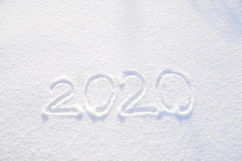 2020 text written on the background of fresh snow texture - winter holiday, Merry Christmas, New Year concept Sunny day royalty free stock photos