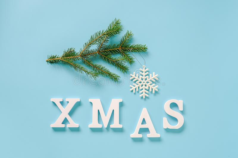 Text Xmas from white letters and christmas decoration snowflake toy on spruce branch, blue background. Concept Merry christmas. Copy space Top view Flat lay stock photos