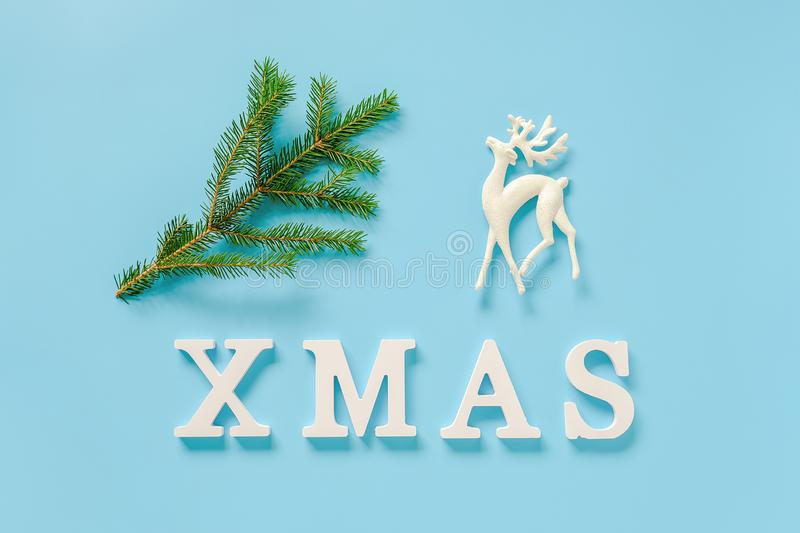 Text Xmas from white letters, green fir branch and christmas decoration deer toy on blue background. Concept Merry christmas. Minimal style Top view Flat lay royalty free stock photography
