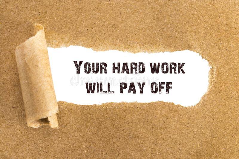 The text Your hard work will pay off appearing behind torn brown. Paper stock photo