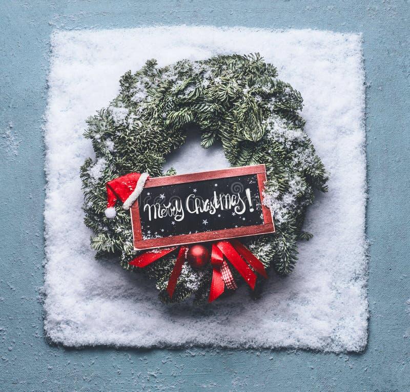 Textbokstäver för glad jul Krans med gröna granfilialer och det röda inramade tecknet och jultomtenhatt i snö på blå bakgrund, bä arkivbild