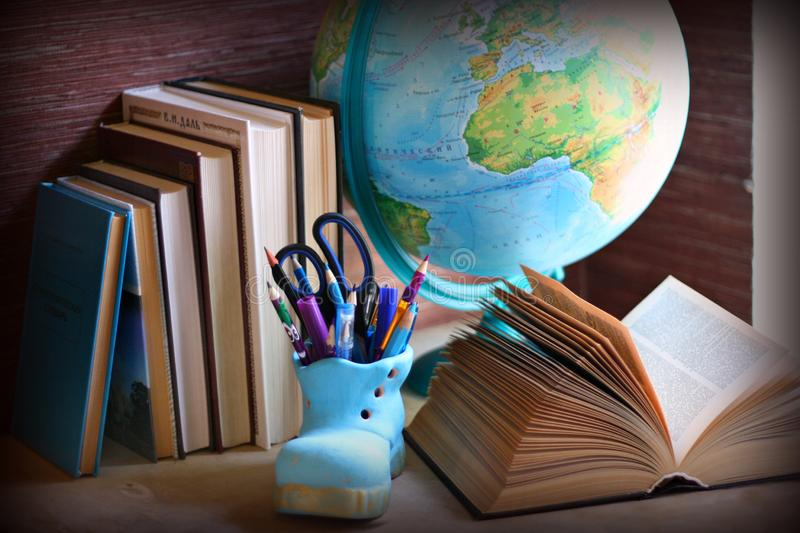 Textbooks, dictionaries, pencil-cup and a globe on the desk. A globe, a pencil-cup and a pile of dictionaries and textbooks as a concept of learning and study royalty free stock photography
