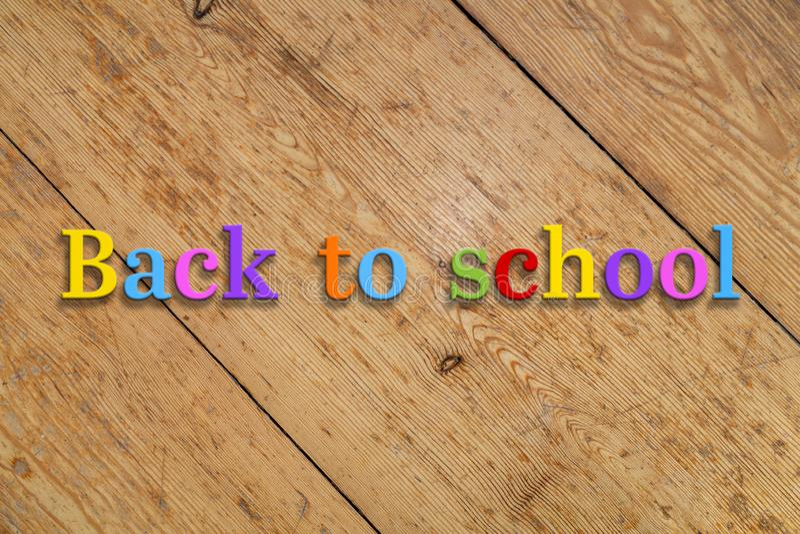 """Texte coloré """"de nouveau à école """"sur un fond en bois image libre de droits"""