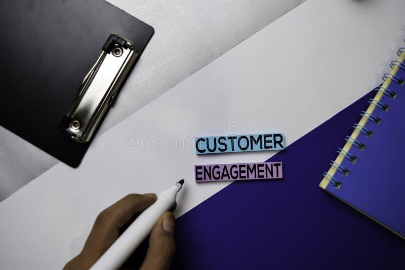Texte d'engagement de client sur les notes collantes avec le concept de bureau de couleur photos stock