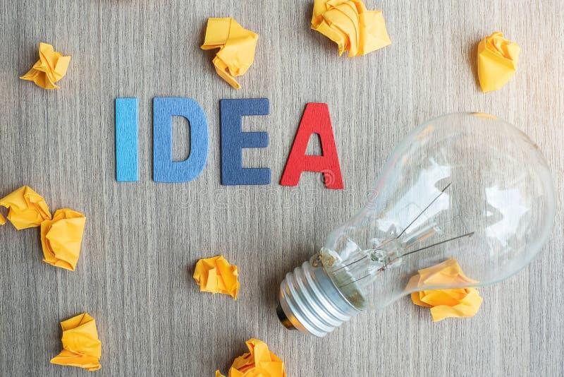 TEXTE d'idée dessus et papier emietté avec l'ampoule sur le fond en bois de table vision, créative, innovation, imagination, insp photo libre de droits