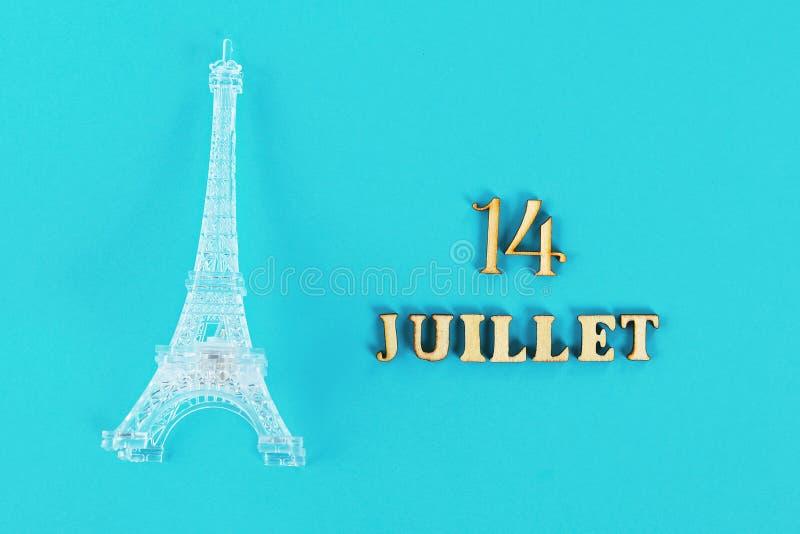 Texte dans le bon 14 juillet français Miniature de Tour Eiffel sur un fond bleu Le concept des vacances le jour de la capture photos stock