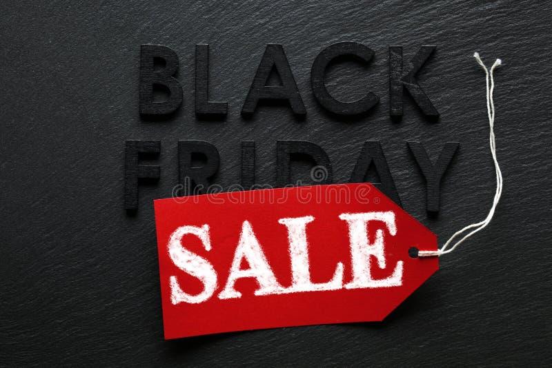 Texte de Black Friday avec l'étiquette rouge de vente sur l'ardoise photos libres de droits