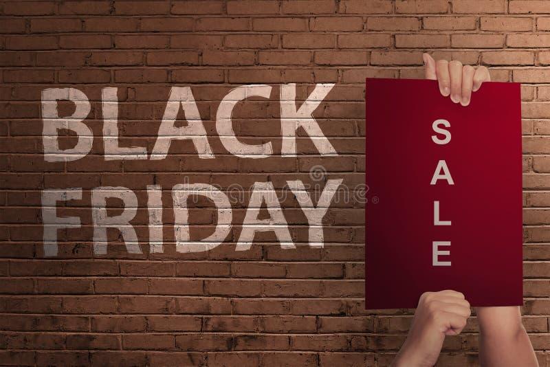 Texte de Black Friday avec la main tenant la bannière de vente images stock