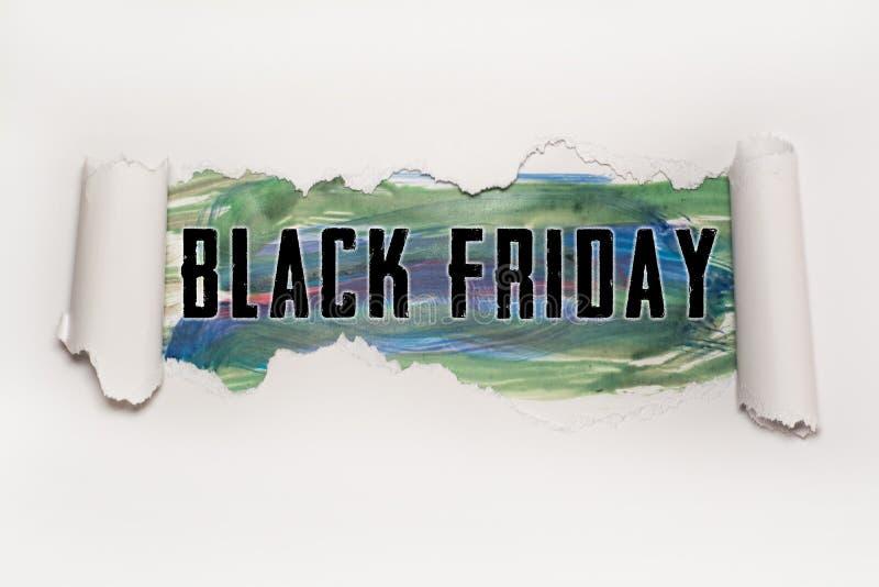 Texte de Black Friday derrière le papier déchiré photographie stock libre de droits