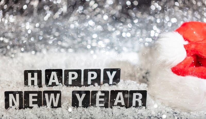 Texte de bonne année sur la neige, fond abstrait de lumières de bokeh photographie stock libre de droits