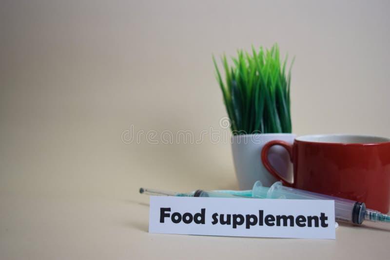 Texte de complément alimentaire, pot d'herbe, tasse de café, seringue, et masque vert de visage photographie stock libre de droits