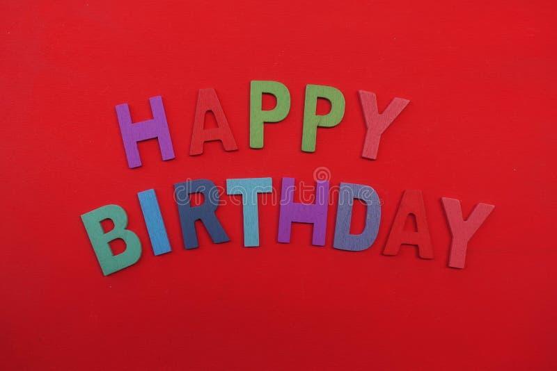 Texte de joyeux anniversaire avec les lettres en bois colorées multi au-dessus de la couleur rouge photo libre de droits