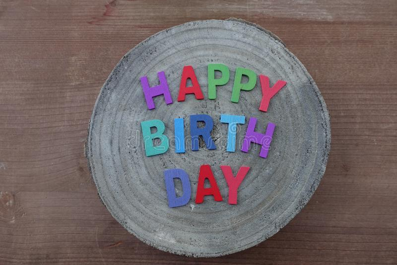 Texte de joyeux anniversaire avec les lettres en bois colorées sur un panneau rond en bois de mangue images libres de droits