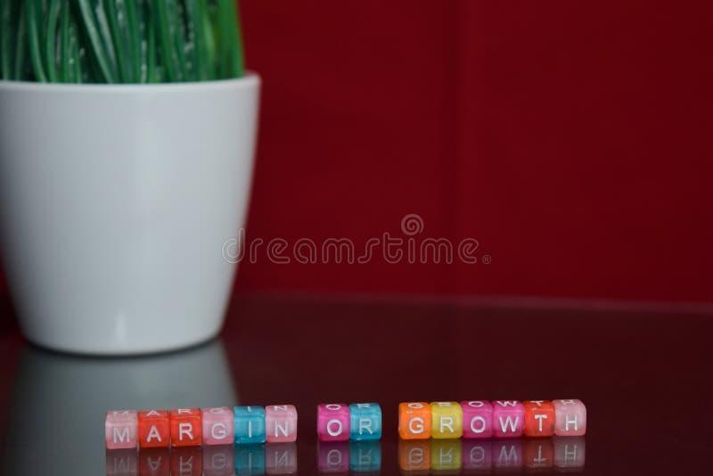 Texte de marge ou de croissance au bloc en bois coloré sur le fond rouge Bureau de bureau et concept d'éducation photographie stock