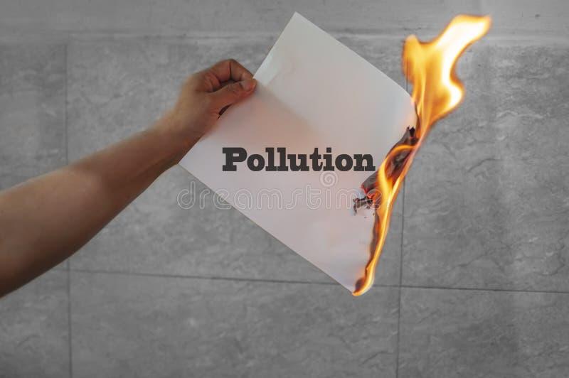 Texte de mot de pollution brûlant avec le feu sur le papier photographie stock