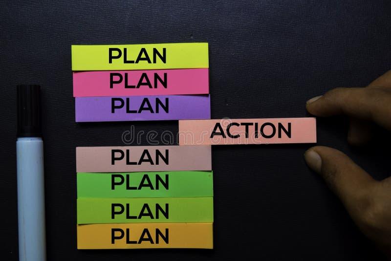 Texte de plan ou d'action sur les notes collantes d'isolement sur le bureau noir Concept de stratégie de mécanisme images libres de droits