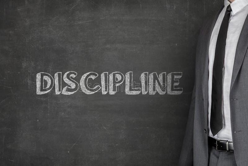 Texte de Standing By Discipline d'homme d'affaires sur le tableau noir photo libre de droits