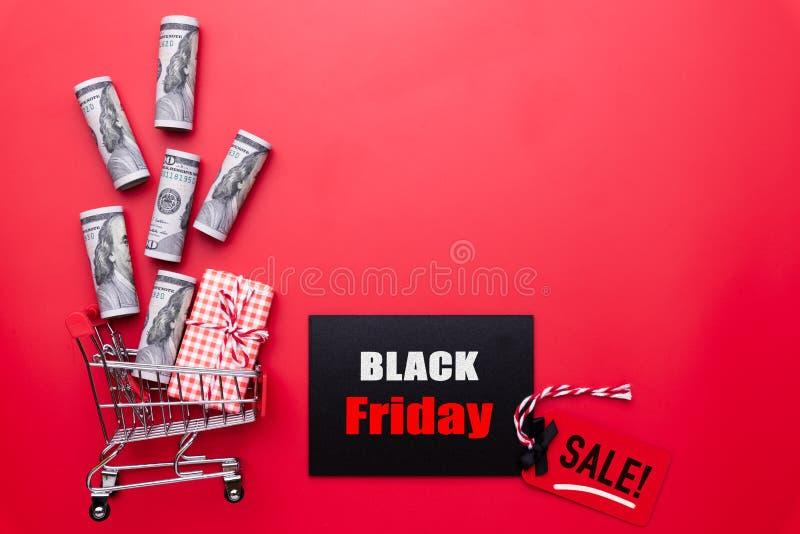 Texte de vente de Black Friday sur une étiquette rouge et noire avec le boîte-cadeau images libres de droits