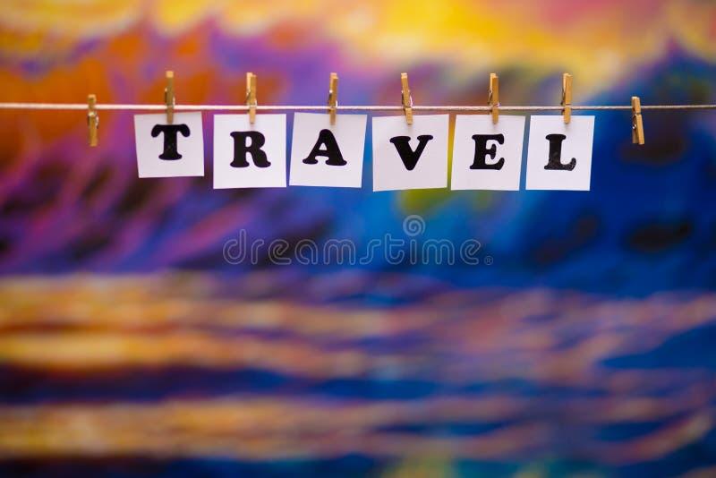 Texte de voyage sur des papiers avec des pinces à linge avec le bokeh de guirlande sur le fond images stock