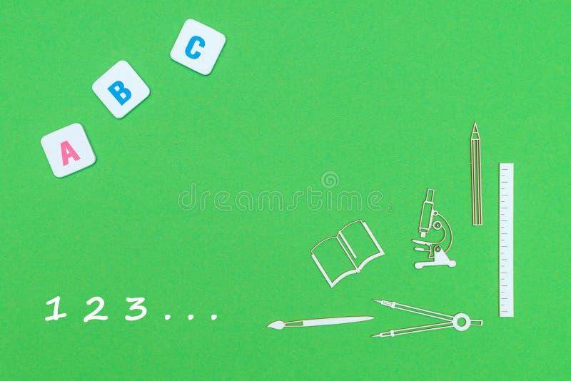 Texte 123, des fournitures scolaires en bois ci-dessus de minitures et des lettres d'ABC sur le fond vert illustration libre de droits