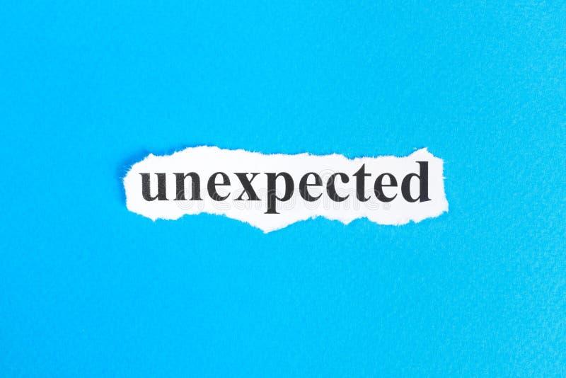 texte inattendu sur le papier Word inattendu sur le papier déchiré texte debout de reste d'image de figurine de concept de COM bo photographie stock