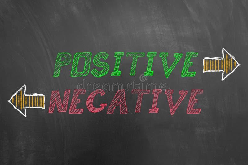 Texte négatif positif avec des flèches sur le tableau noir photos libres de droits